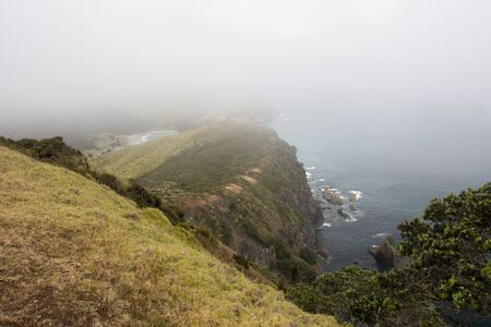 A misty view of the Te Paki Coastal Track in Northland, New Zealand covered in low lying clouds. In the distance Tapotupotu Bay is visible from the seaside ridge trail on top of the mountains. Stock Photo - 136910586