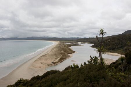 The beach and estuary of Spirits Bay on the Cape Reinga, Northland, New Zealand on a cloudy day.