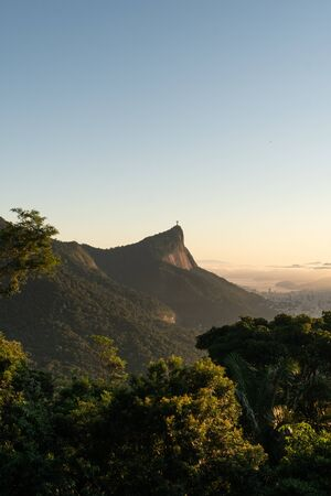 Golden light from the sunrise on the Christ the Redeemer statue on Corcovado mountain, from the Vista Chinesa lookout in the Tijuca Forest of Rio de Janeiro. The sky is blue and trees frame the view. Stock Photo