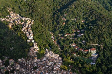 An aerial view over the favela of Rocinha alongside an expensive private school showing the wealth gap and income inequality of Rio de Janeiro, Brazil, where the poor and rich live side by side.