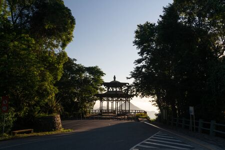 A clear blue sky sunrise over the Vista Chinesa Rotunda lookout in the Tijuca Forest mountains of Rio de Janeiro, Brazil. The shelter is silhouetted and viewed from the road surrounded by trees.