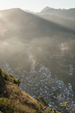 A sunset aerial view of cloud over the Tijuca Forest mountain range and Rocinha Favela in Rio de Janeiro, Brazil, from Dois Irmaos. Expensive suburb alongside shows the wealth gap and inequality.