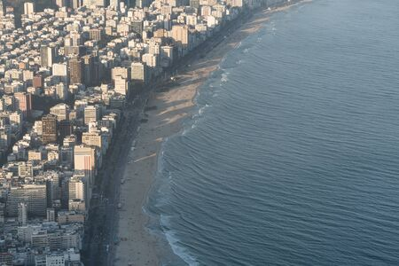Aerial view from Morro Dois Irmaos Two Brothers Hill looking down over Leblon and Ipanema Beach and suburb during golden hour in Rio de Janeiro, Brazil. There are dense expensive buildings and hotels Stock Photo