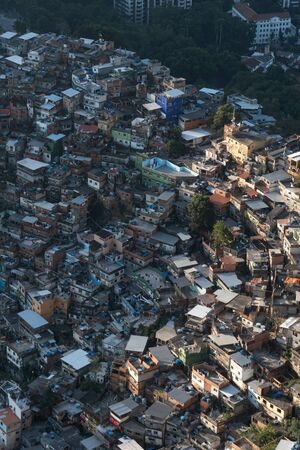 An aerial view looking down on the Rocinha Favela in Rio de Janeiro, Brazil, from the top of Dois Irmaos Mountain. The dense slum is full of brick houses, winding roads and poverty beside rich areas. Stock Photo