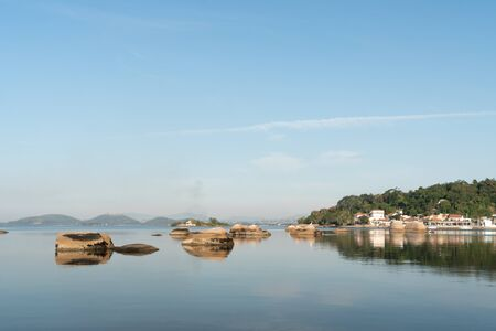 Rocks reflected in the calm blue waters of Ilha de Paqueta in Guanabara Bay, Rio de Janeiro. There is a small village wth colonial architecture, white buildngs, tile roofs and a tree covered hill. Stock Photo