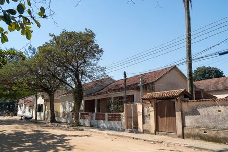 A quiet dirt road on the Ilha de Paqueta Island in Rio de Janeiro. The residential street has old colonial houses with tile roofs, front walls, gates and trees on a sunny afternoon with blue sky.