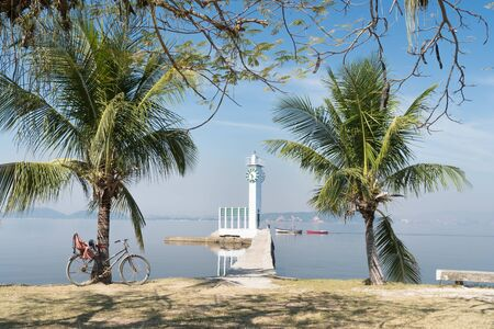 A white clock tower lighthouse at the end of a narrow concrete pier on Ilha de Paqueta Island, Rio de Janeiro. There are palm trees either side, with calm blue sea, small fishing boats and a bike.