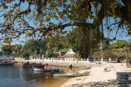 The waterfront on Ilha de Paqueta Island, Rio de Janeiro, There is calm brown water, a small white sand beach, overhanging tree, small colored fishing boats, blue sky and white buildings on a street.