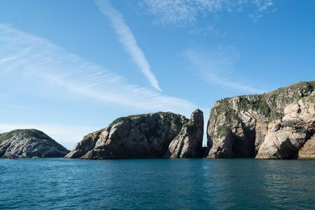 The phantom blue deep sea, sky and rock mountains on a boat tour off the coast of Arraial do Cabo, Rio de Janeiro. There is a narrow vertical gap in the middle of the rocks on a sunny afternoon. Stock Photo