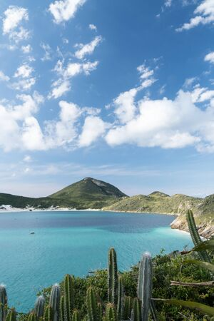 View from the hiking trail at Arraial do Cabo, at the end of the Prainhas do Pontal do Atalaia Beach Small Beaches, overlooking Ilha do Farol. There are cactuses and turquoise water on a sunny day. Stock Photo