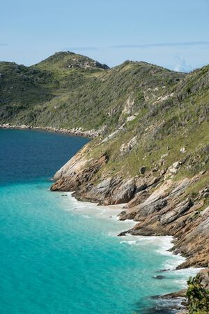 View over the peninsula at the end of the Prainhas do Pontal do Atalaia Beach Small Beaches, Arraial do Cabo. The mountains end in the sea and a line is visible between dark and light turquoise water.
