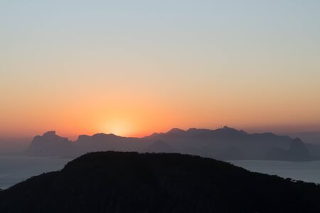 A clear sky orange Sunset from the Costao de Itacoatiara rock mountain in Niteroi, Rio de Janeiro, Brazil. The sun is dipping over the horizon of the Tijuca Forest and Pedra da Gavea mountains beyond