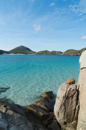 The calm turquoise tropical waters of Prainhas do Pontal do Atalaia Beach in Arraial do Cabo in Rio de Janeiro, Brazil, framed by tall rocks with Ilha do Farol and the dry peninsula mountains beyond.