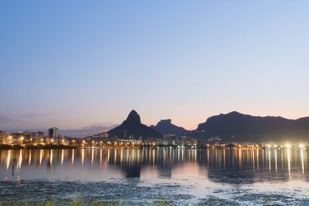 Sunset from the lakeside edge of Lagoa Rodrigo de Freitas in Rio de Janeiro, with clear blue and pink sky and street lights. Dois Irmaos Mountain and Pedra da Gavea are reflected in the lake water.