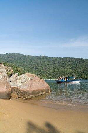 Early morning at Praia do Pouso Beach, Ilha Grande island in the state of Rio de Janeiro, Brazil, on the trail to Praia Lopes Mendes. There is golden sand, rocks, a boat, green mountains and blue sky.