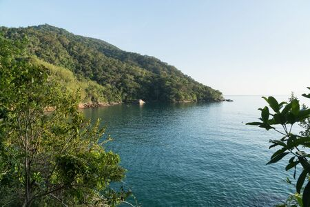 Early morning view at the lookout over Praia de Mangues Beach, Ilha Grande island, state of Rio de Janeiro, Brazil, from the trail to Praia Lopes Mendes. There is green mountains, blue sea and sky.
