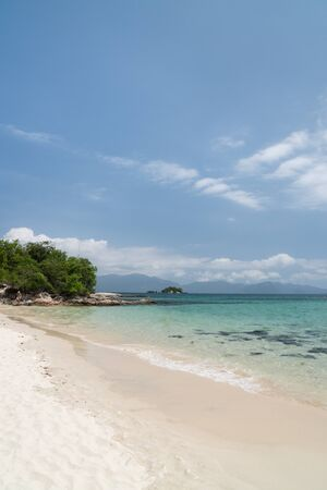 Tropical beach on the island Ilha Cataguas off the coast of Angra dos Reis in the state of Rio de Janeiro, Brazil. There is calm turquoise water, white sand, rocks, trees, blue sky and mountains. Stock Photo
