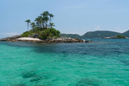 Tiny cliche tropical islands of Ilhas Paradisiacas off the coast of Ilha Grande in Angra dos Reis in the state of Rio de Janeiro. They have palm trees, white sand, rocks and turquoise tropical water.