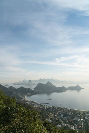 Evening view from the Parque da Cidade City Park lookout in Niteroi, overlooking Guanabara Bay and the city of Rio de Janeiro. There is blue sky, and mountains such as Sugarloaf and Dois Irmaos. Stock Photo