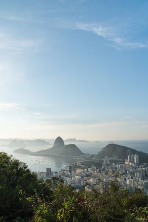 Sunrise view over Sugarloaf Mountain and Guanabara Bay from Mirante Dona Marta in Rio de Janeiro. The early morning golden light shines over the sea and the buildings of the Botafogo suburb and trees