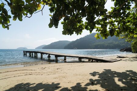 Early morning at Praia do Pouso Beach, Ilha Grande island in the state of Rio de Janeiro, Brazil, on the trail to Praia Lopes Mendes. A timber wharf is framed by hanging silhouetted tree leaves.