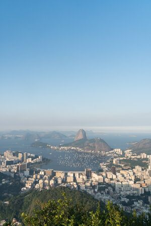 View over Sugarloaf Mountain, Botafogo suburb and Guanabara Bay from Mirante Dona Marta lookout, Rio de Janeiro on a clear evening with blue sky. The hill casts a shadow on the tall apartment buidings