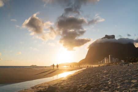 A golden sunset from Sao Conrado Beach in the city of Rio de Janeiro, Brazil. Pedra da Gavea, a tall granite rock mountain sits at the end of the urban beach, with a tidal river in the white sand. Stock Photo