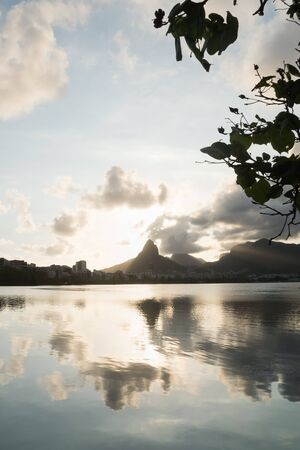 A sunset, blue sky, clouds, Pedra da Gavea and Morro Dois Irmaos Two Brothers Hill are reflected in the waters of Lagoa Rodrigo de Freitas Lake in Rio de Janeiro, framed by silhouetted tree leaves. Stock Photo