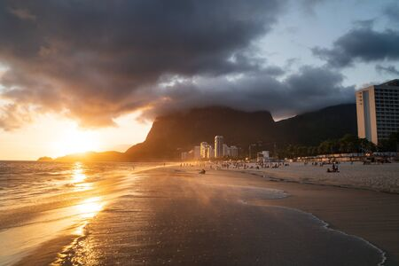 A dramatic sunset from Sao Conrado Beach, Rio de Janeiro, Brazil. There are low lying clouds around the tall granite rock mountain Pedra da Gavea and golden light on the white sand and buildings.
