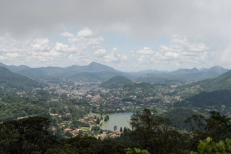 Aerial view over the valley and green mountain city of Teresopolis in the state of Rio de Janeiro, Brazil. Photo taken from the nearby Pedra do Elefante, of the buildings and trees on a cloudy day.