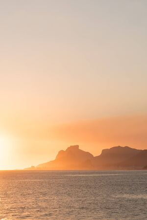 A golden sunset with orange clouds and blue sky over Pedra da Gavea and the mountains of the Tijuca Forest in Rio de Janeiro from Piratininga Beach in Niteroi, the city across the Guanabara Bay.