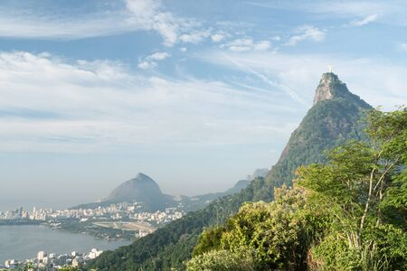 View of Corcovado Mountain and Christ the Redeemer Statue from Mirante Dona Marta. The morning blue sky has clouds, with Morro Dois Irmaos and the lake.