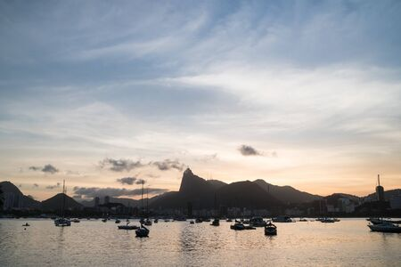 Sunset from Mureta da Urca, over the Tijuca Forest mountains and Christ the Redeemer Statue on Corcovado. There are wispy clouds, golden light and boats.