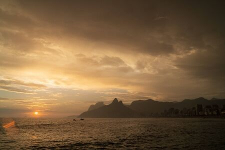 A dramatic yellow and orange moody sunset over Ipanema Beach and Morro Dois Irmaos Two Brothers Mountain in Rio de Janeiro. There is a low sun with golden light shining up onto dramatic stormy clouds