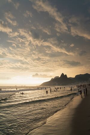 A dramatic sunset over Ipanema Beach in Rio de Janeiro, Brazil,with golden light from the low angle sun shining up onto the stripes of grey clouds. There are silhouettes of people swimming in the sea. Stock Photo