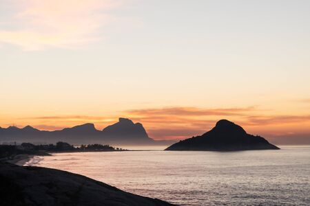 Golden sunrise from Mirante do Roncador over Recreio Beach, Pedra do Pontal, Pedra da Gavea and the Tijuca Forest mountains of Rio de Janeiro. There are orange clouds at dawn with silhouetted rocks.