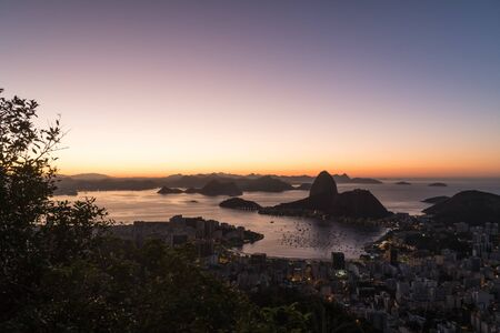 Sunrise from Mirante Dona Marta in Rio de Janeiro overlooking Sugarloaf Moutain, the suburb of Botafogo Guanabara Bay and Niteroi in the distance. There is orange light and a clear sky at dawn.