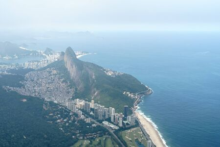 View from the summit of Pedra da Gavea, Rio de Janeiro over Sao Conrado Beach, the favela Rocinha and Dois Irmaos, Two Brothers Mountain. The sea is blue and there is low lying cloud in the sky. Stock Photo