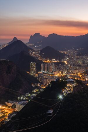 A pink sunset view at dusk over the night street lights of the city and buildings of Rio de Janeiro from Sugarloaf Mountain. A cable car travels from Morro da Urca. Botafogo, Pedra da Gavea are beyond