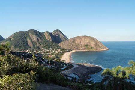 View over Itacoatiara Beach from the Morro das Andorinhas mountain hike in Niteroi, Rio de Janeiro. The sea and sky are bright blue with the Elephant Rock and Costao steep mountain peaks beyond.