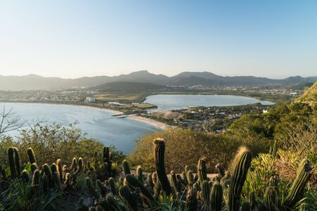 View over Itaipu Beach in Niteroi, Rio de Janeiro, from the Morro das Andorinhas hike. The early evening light hits the trees, cactuses, lake, white sand and mountains in the blue sky.