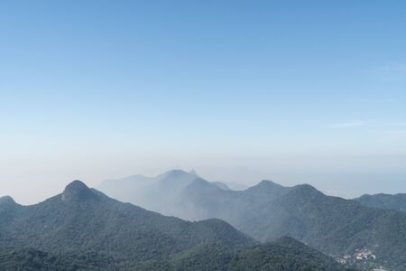 View from a lookout on the hiking trail over the mountains of the Tijuca Forest in Rio de Janeiro. There is blue sky and city haze on a sunny morning. The urban jungle has steep green peaks.