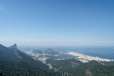 Aerial view over the city of Rio de Janeiro from the Pedra da Proa rock on a hiking trail in the mountains of the Tijuca Forest. There is Corcovado, Ipanema and Lagoa Rodrigo de Freitas and blue sky.