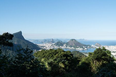 Aerial view over the city of Rio de Janeiro from the Vista Chinesa lookout in the Tijuca Forest. There are green trees, Corcovado, Sugarloaf Mountain and Lagoa Rodrigo de Freitas on a sunny afternoon Stock Photo