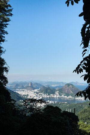 Aerial view over the city of Rio de Janeiro from the Pedra da Proa rock on a hiking trail in the mountains of the Tijuca Forest. There is Sugarloaf, Lagoa Rodrigo de Freitas and blue sky and trees. Stock Photo