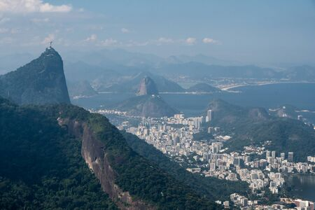 Aerial view of Corcovado, Sugarloaf Mountain and the white buildings and city of Rio de Janeiro on a sunny hazy day. Taken from a lookout in the Tijuca Forest crossing. The city of Niteroi is beyond. Stock Photo