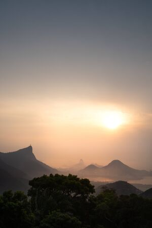 Peach sun rays peak out from behind the clouds during a dramatic sunrise from Vista Chinesa in the Tijuca Forest of Rio de Janeiro, with the silhouette of Christ the Redeemer and Sugarloaf Mountain . Stock Photo