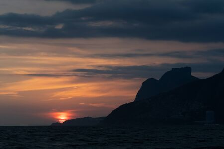 A dramatic orange sunset in Rio de Janeiro beside the silhouette of Pedra da Gavea rock mountain. The large red sun is sinking over the horizon and there are layers of clouds around the peak at dusk.