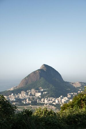 Morro Dois Irmaos mountain in the early morning light seen from Mirante Dona Marta, Rio de Janeiro. The sky is blue and the suburb of Gavea, and the favelas of Rocinha and Vidigal show inequality. Stock Photo