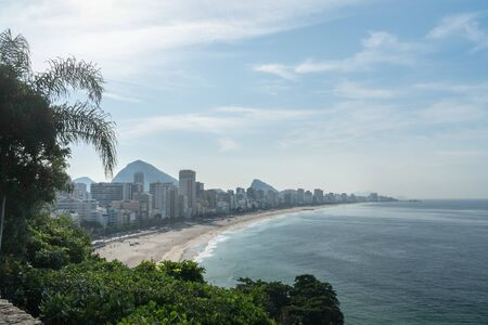 View from the Parque Natural Municipal Penhasco Dois Irmaos Park in Rio de Janeiro looking over Leblon and Ipanema Beach on a sunny day. There are expensive seaside hotels and apartment buildings. Stock Photo